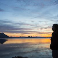 Student looking out onto a sunset over the water at the Alaska Salmon Camps