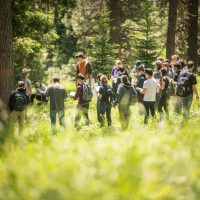 Students gathered around in a circle, on a field trip in a forest
