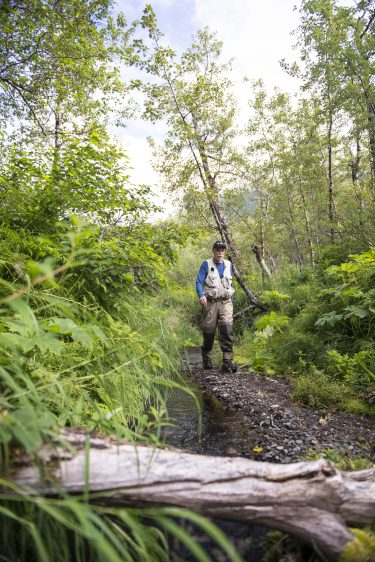 Ray Hilborn hiking next to a stream in Bristol Bay.