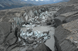 A close-up view of the ice-walled canyon at the terminus of the Kaskawulsh Glacier, with recently collapsed ice blocks. This canyon now carries almost all meltwater from the toe of the glacier down the Kaskawulsh Valley and toward the Gulf of Alaska.
