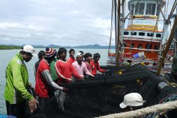 Young migrant fishers pulling and cleaning nets on fishing boats in Thailand.