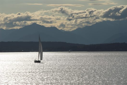 Sail boat in Puget Sound waters with mountains in the background.