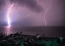 Lightening strikes water in background. Aircraft carrier with jets sitting on it in foreground.