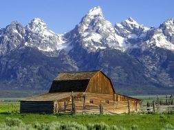 Snowcapped mountains in the distance with a wooden barn in foreground.