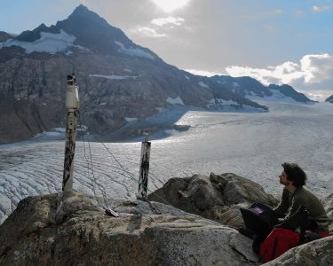 Student sitting alongside large rocks with scientific equipment set up around him, large glacier and mountains in the background.