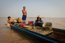 Three Cambodian fisherpeople on a long, narrow boat with fishing lines and baskets. They are on the rough, brackish water of Tonle Sap Lake.