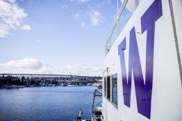 """The side of a large boat with a purple UW """"W"""" painted on it, water and bridge in background."""