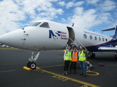 Roger Marchand with UW students Litai Kang (left) and Emily Tansey (center) in front of the Hiaper research aircraft.