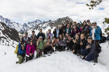 A group of about 30 students in hiking gear pose with their professor in the snow at the top of a Cascade mountain peak
