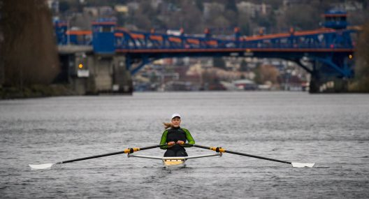 Female rower wearing a hat and wetsuit rows on Lake Washington with Fremont Bridge behind her.