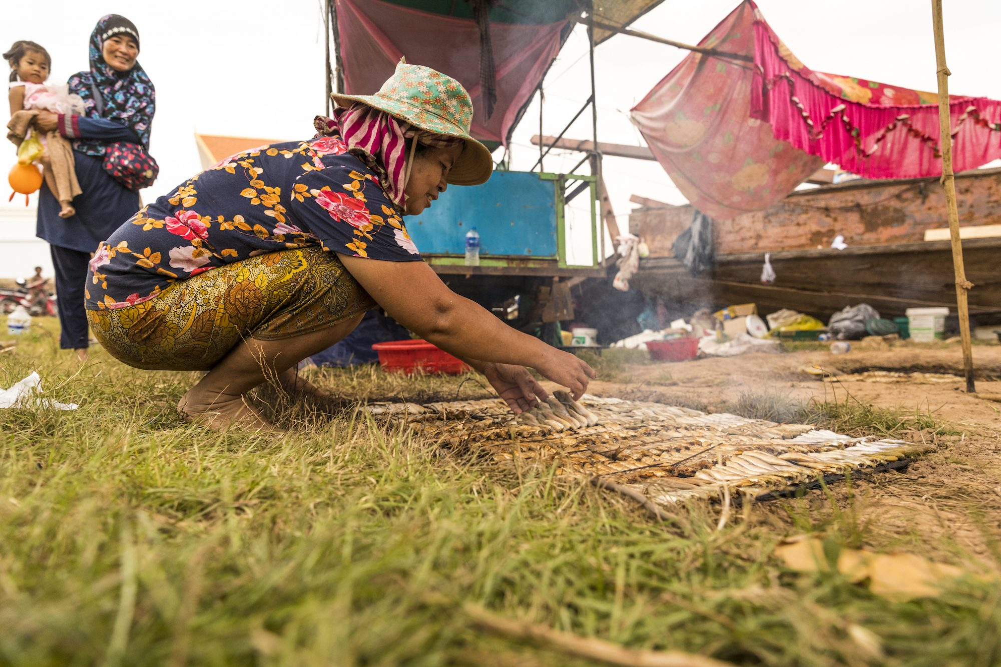 A woman cooks rows of small fish on the ground. An older woman holding a toddler looks on