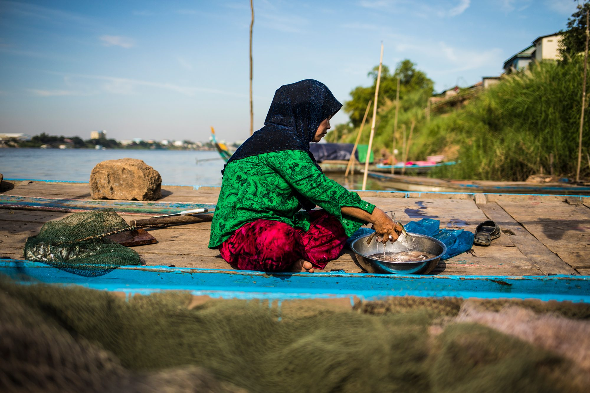 A woman in a hijab sits in a fishing boat near the shore and washes small fish in a metal bowl