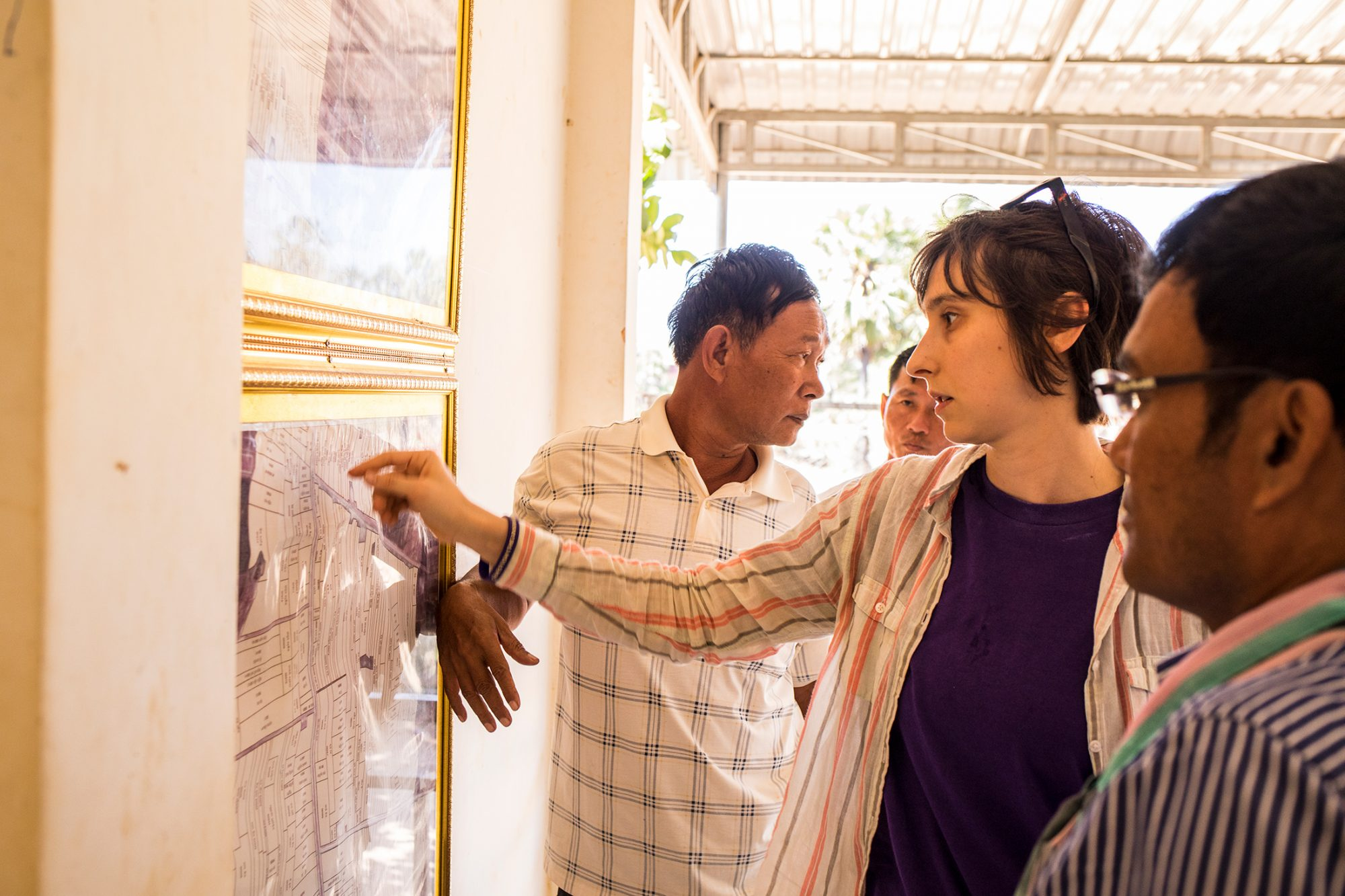 Three Cambodian farmers and Yasmine gather around a faded purple map posted on the wall