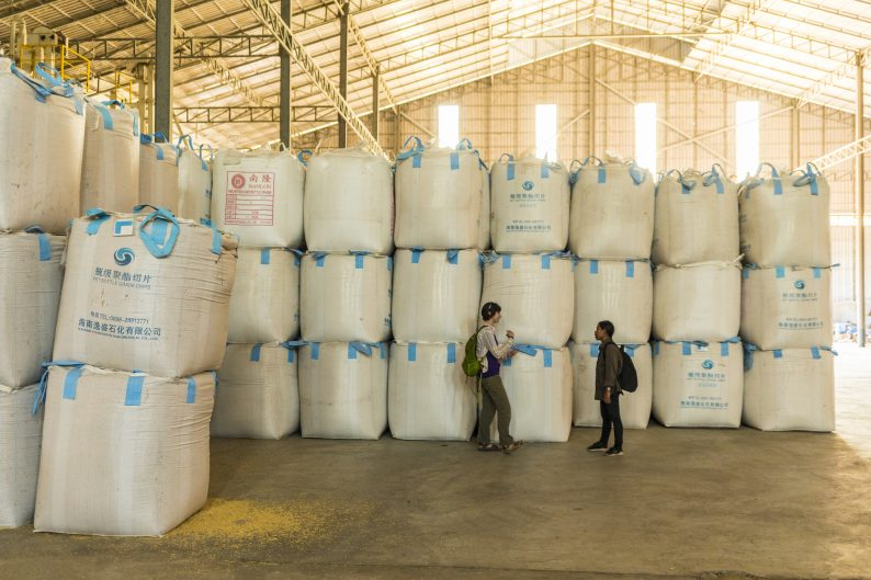 Yasmine and E-Nieng talk in a warehouse surrounded by huge containers of rice stacked 10 feet high