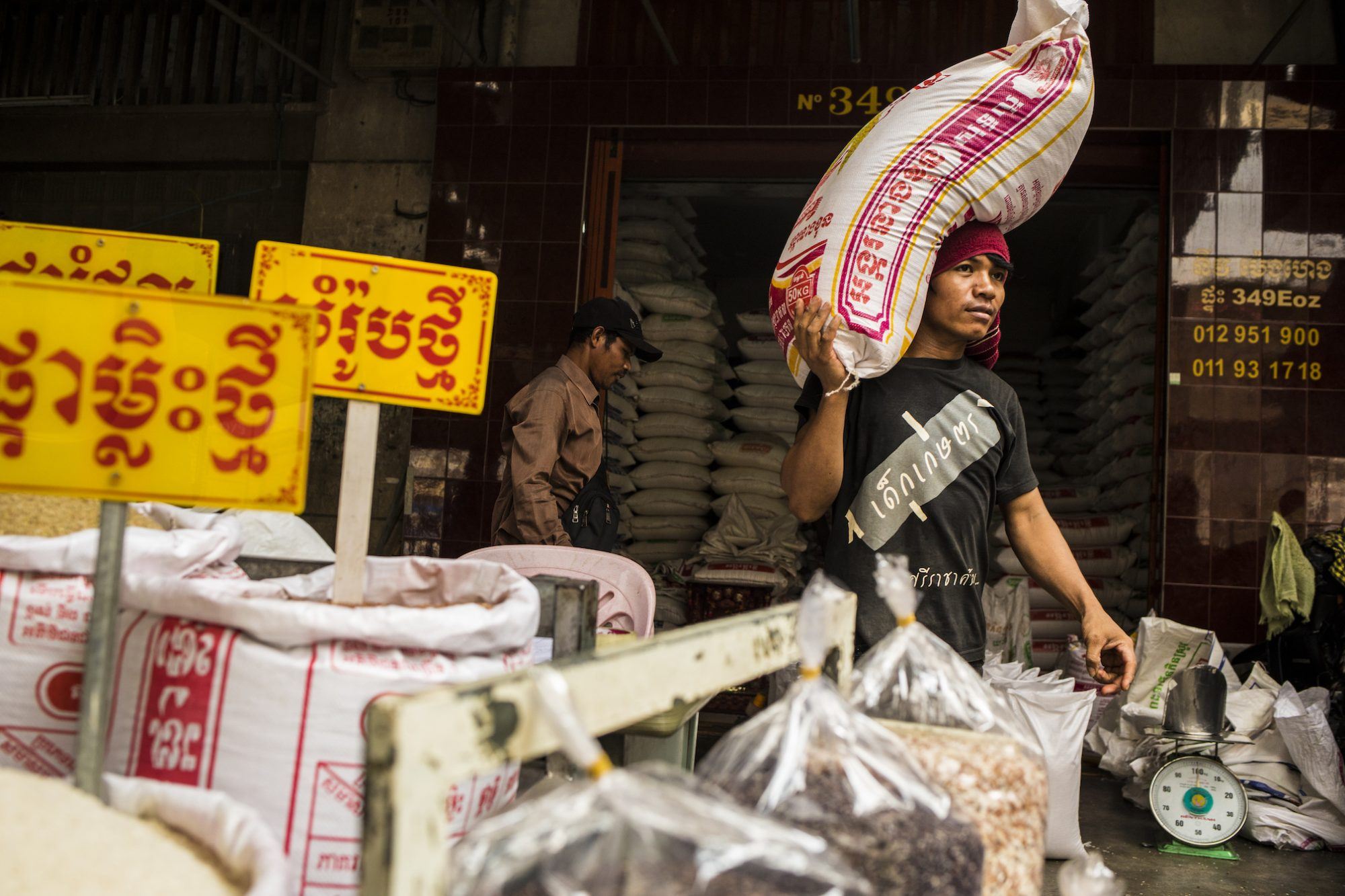 A man in a head scarf carries a huge bag of rice on his shoulder in a colorful rice market