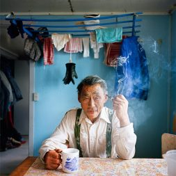 Older man sitting at kitchen table with a coffee mug and cigarette.