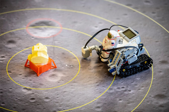A Lego Mindstorms robot, with a plastic astronaut strapped to the front, approaches the lunar lander.